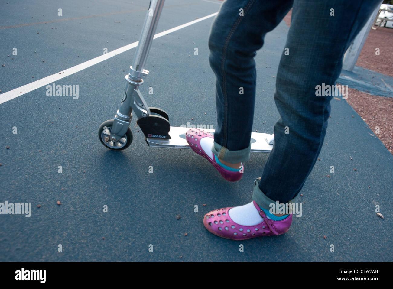 Menina vestindo sandálias de cor-de-rosa a cavalo uma scooter Imagens de Stock