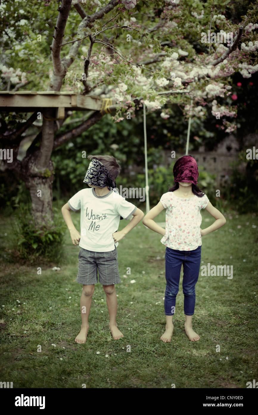 Crianças brincam vestindo blinfolds. Imagens de Stock