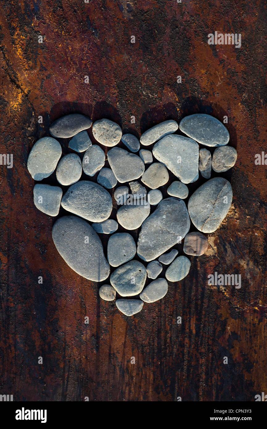 Formato de coração seixos sobre um fundo de ardósia de textura Imagens de Stock