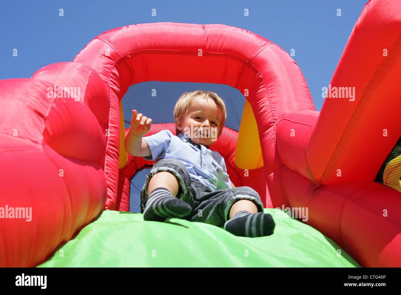 Criança na almofada insuflável castelo insuflável deslize Imagens de Stock