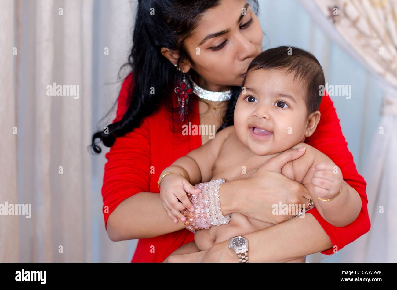 Mãe beijando seu bebê indiano menina, interior Imagens de Stock