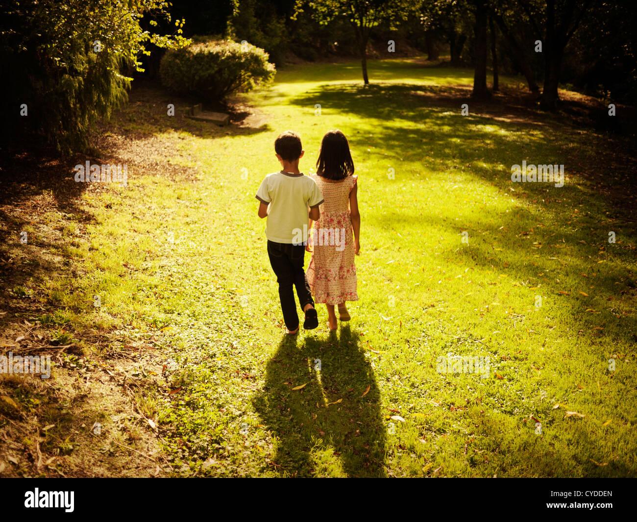 Hora de ouro: boy e a garota verão caminhada à tarde no bosque Imagens de Stock