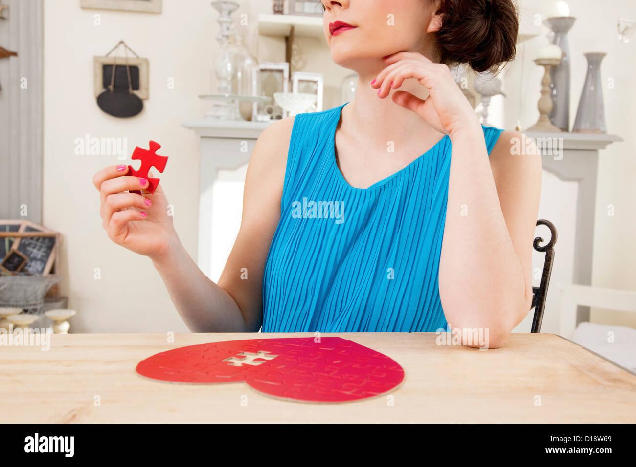 Mulher fazendo puzzle em forma de coração exploração pedaço Imagens de Stock