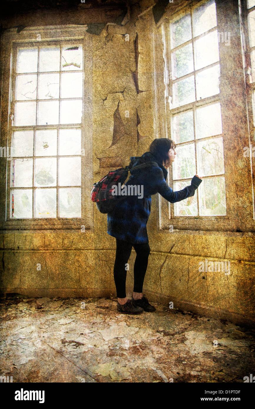 Medo mulher olhando para fora de uma janela Imagens de Stock