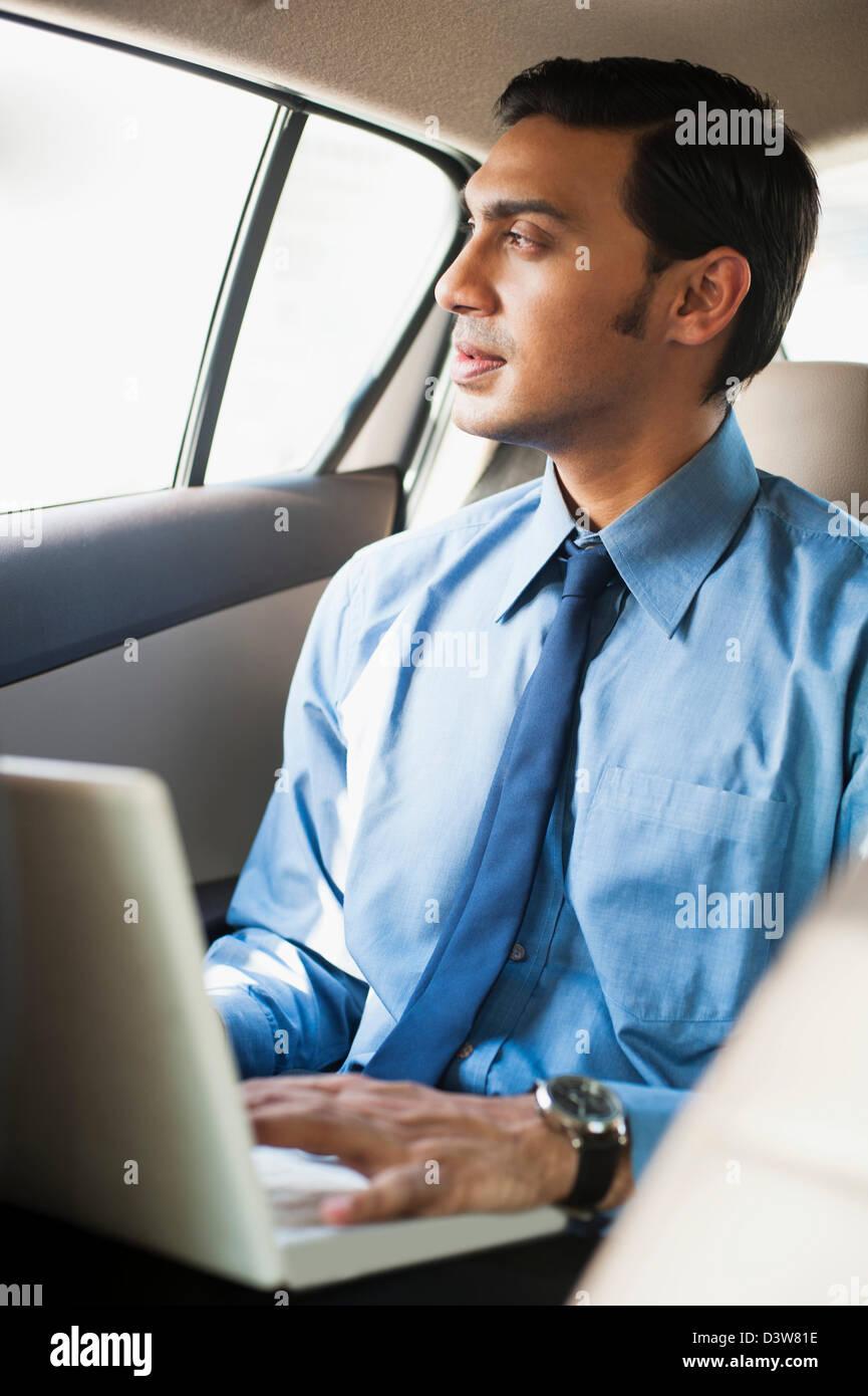 O bengali empresário usando um laptop em um carro Imagens de Stock