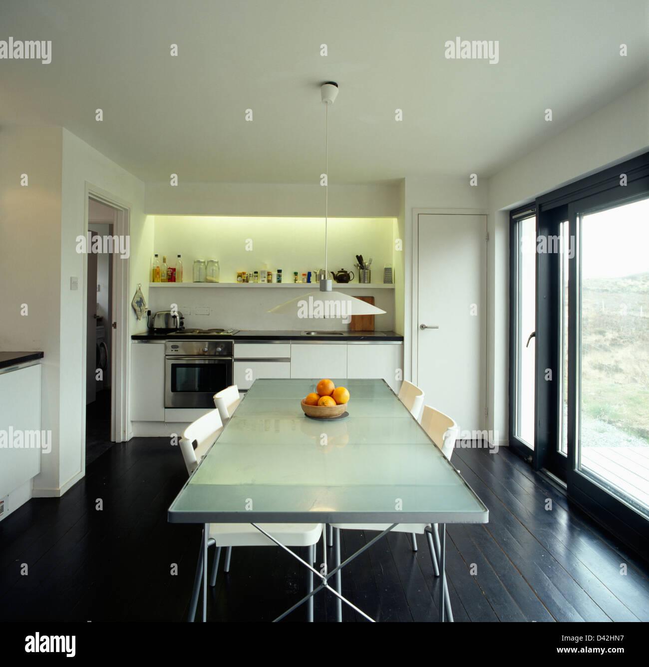 Cadeiras Brancas Na Mesa Com Tampo De Vidro Opaco Na Cozinha Moderna