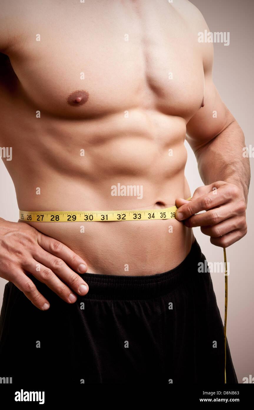 333541eb1 Aplicar o homem medindo a sua cintura depois de um treino no ginásio ...
