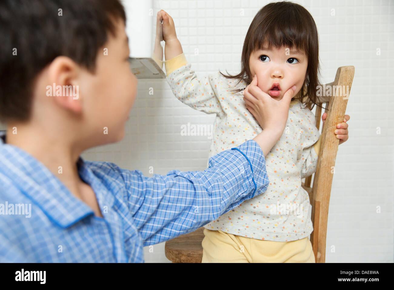 Travesso irmão jovens irmãs enfrentam Imagens de Stock