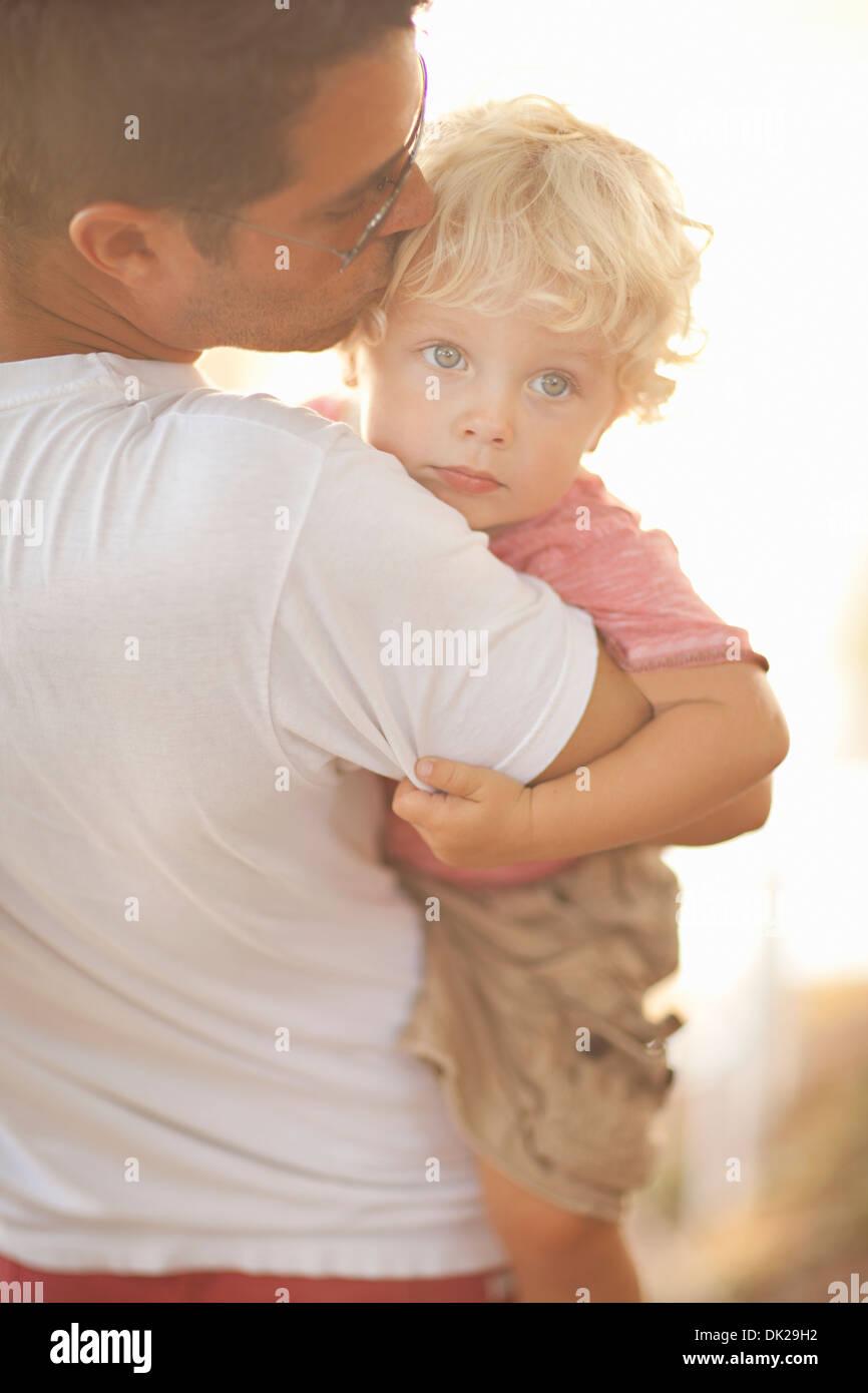 Pai transportando toddler filho e reconfortante beijando fronte Imagens de Stock
