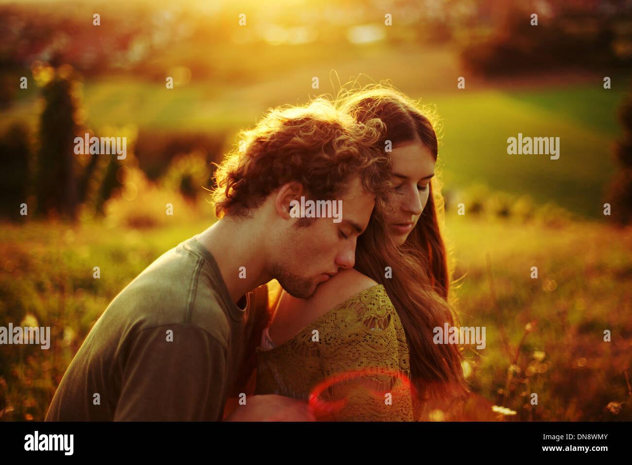 Jovem casal no amor abraçando num meadow Imagens de Stock