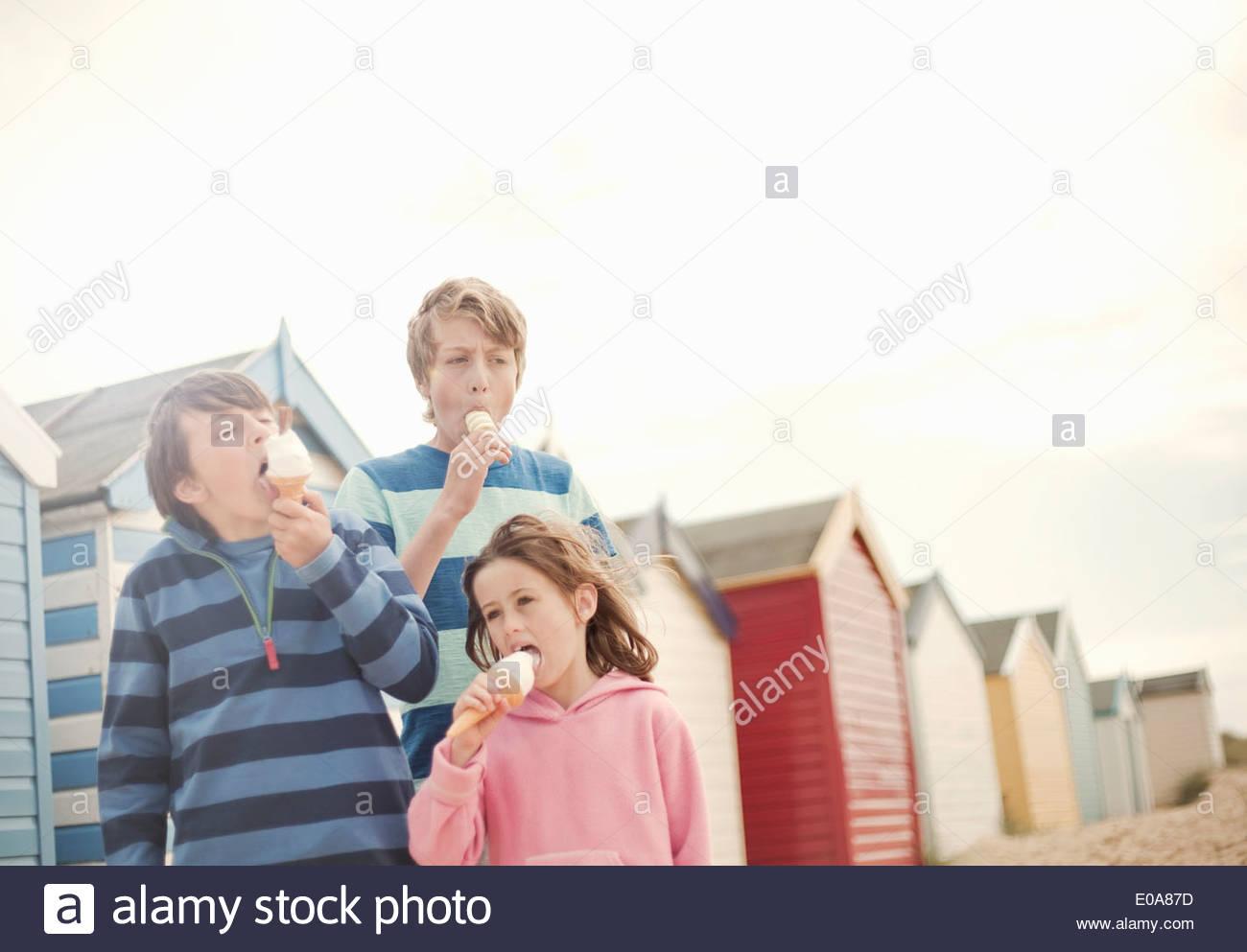 Três crianças ao lado de cabanas de praia comer gelados cones, Rochdale, Sussex, Reino Unido Imagens de Stock