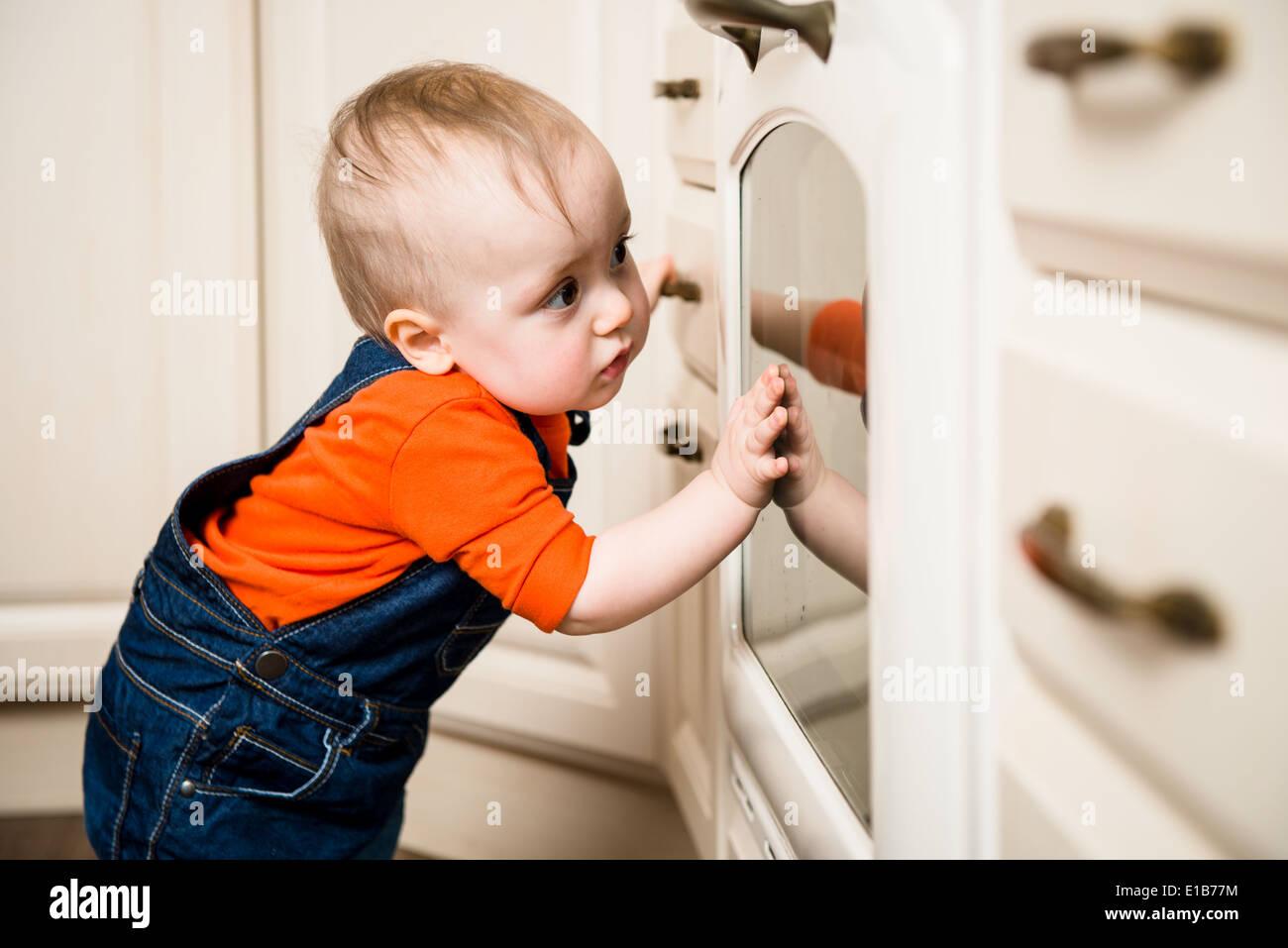 Bebé curioso ver através de vidro do forno de cozinha Imagens de Stock