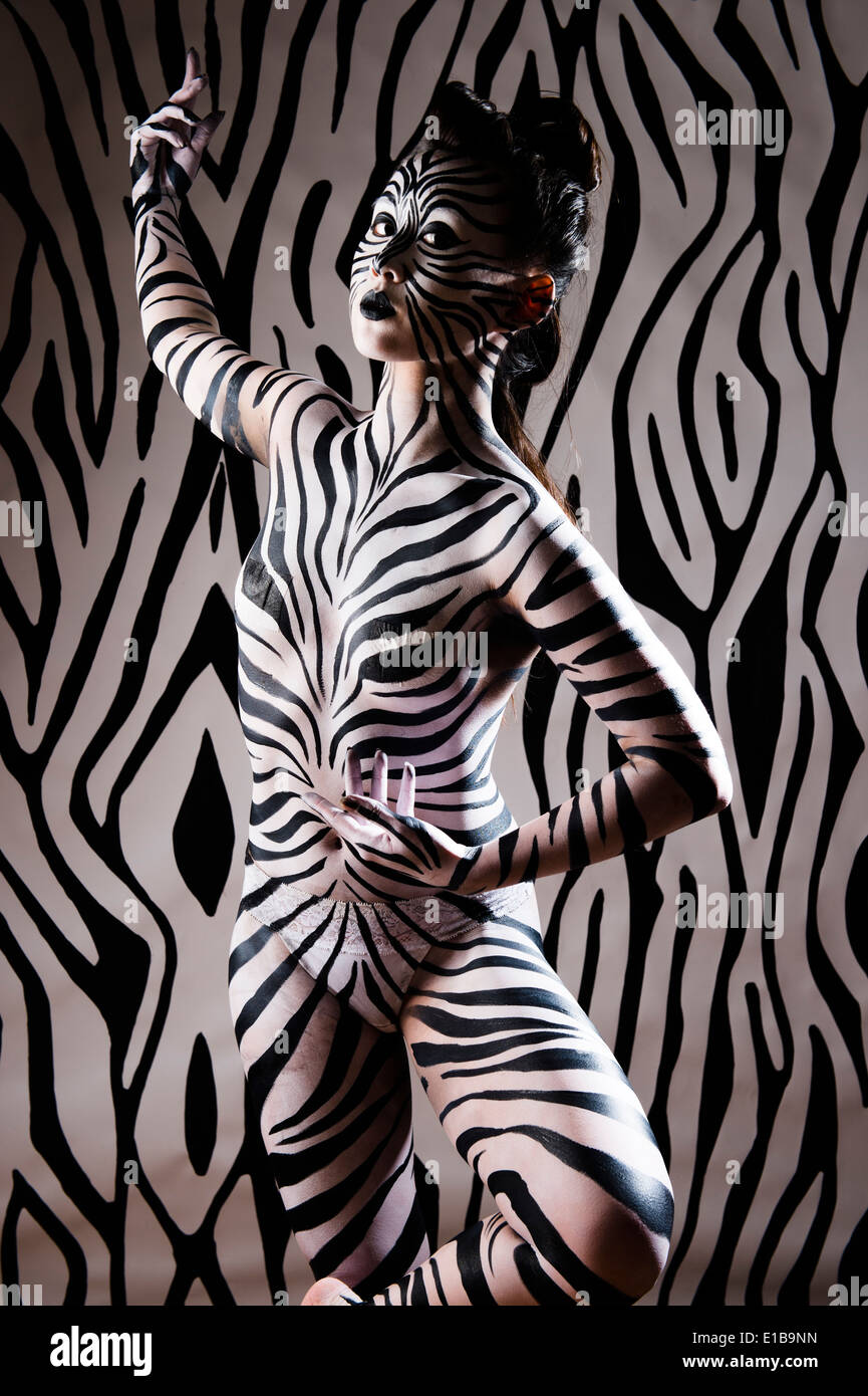 A woman with her body painted in black and white zebra stripes to