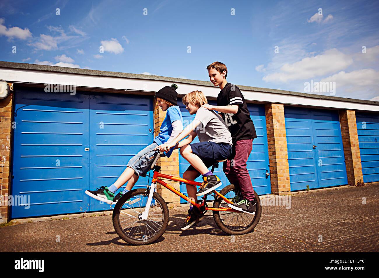 Menino dando dois amigos um passeio em bicicleta Imagens de Stock