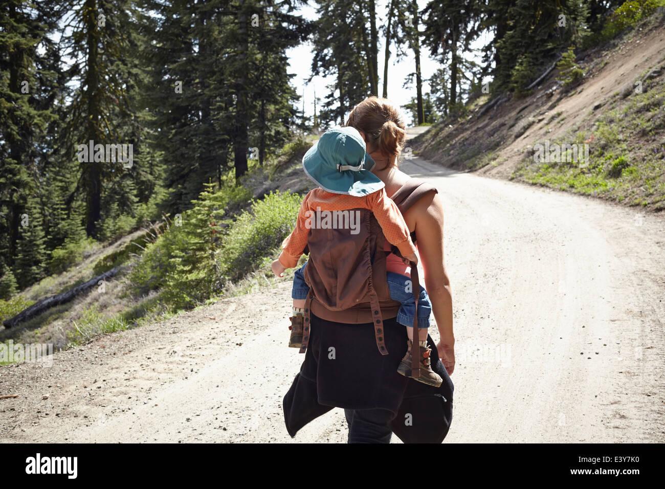 Vista traseira da mãe que transporta criança no transportador do bebé Imagens de Stock