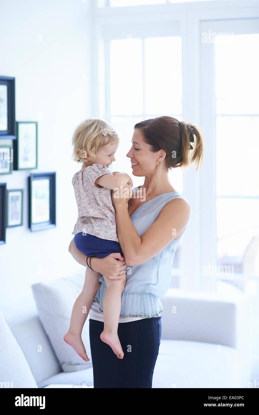 Meados de mulher adulta e criança filha na sala de estar Imagens de Stock
