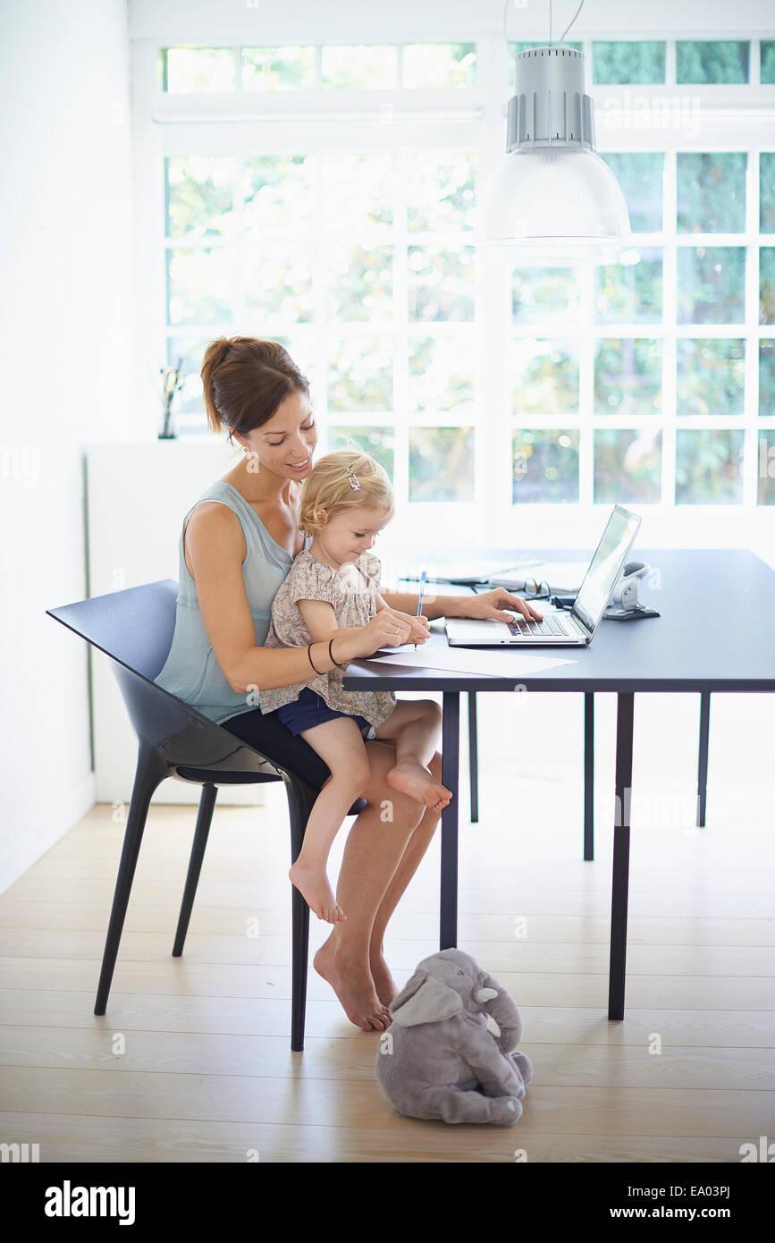 Meados de mulher adulta e criança filha digitando no laptop Imagens de Stock
