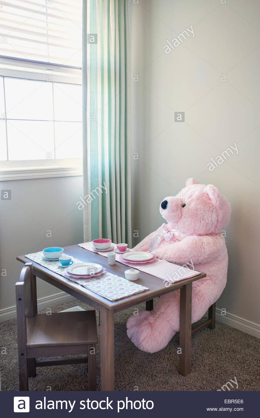Rosa ursinho sentado na mesa de chá para crianças Imagens de Stock