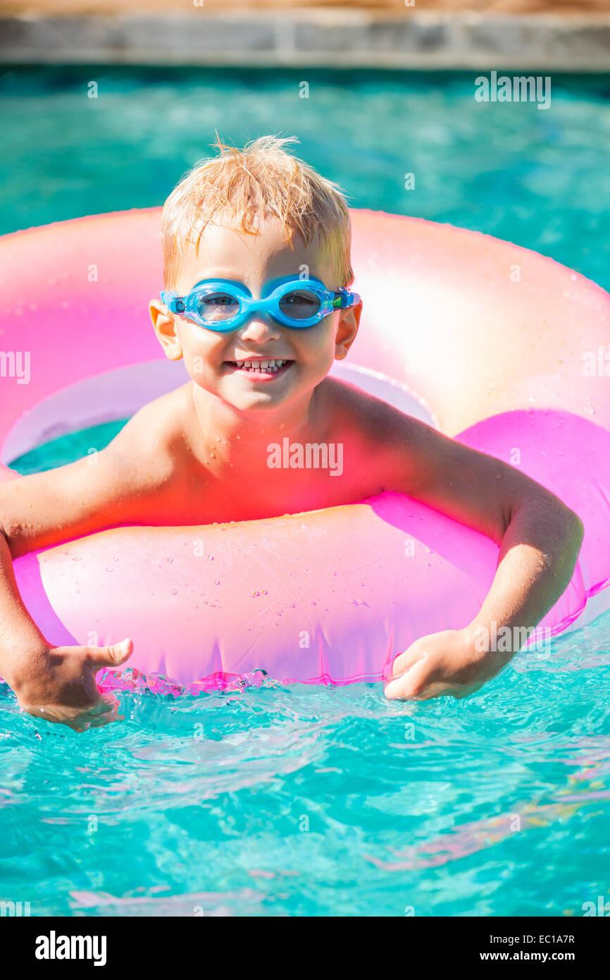 Miúdo divertem na piscina, com óculos e de jangada. Férias de verão diversão. Imagens de Stock