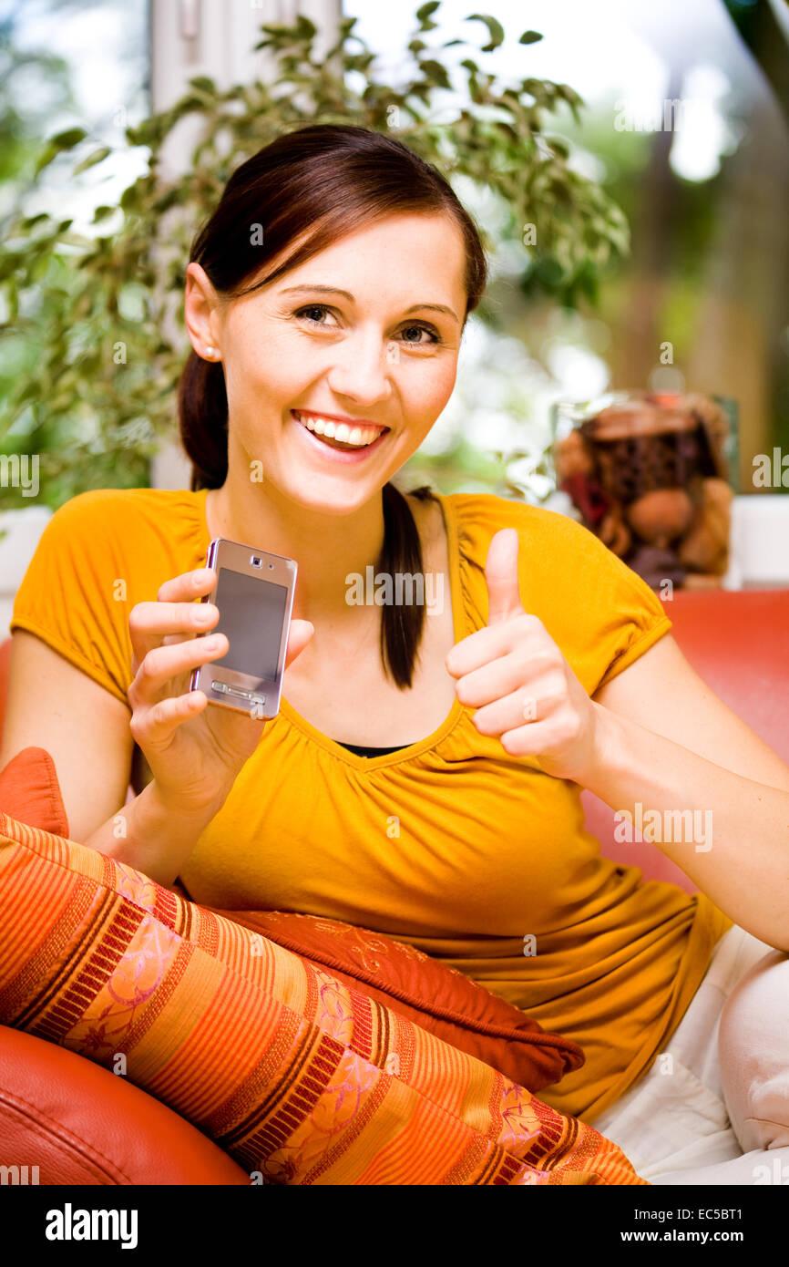 Junge Frau mit dem prático im Wohnzimmer Imagens de Stock