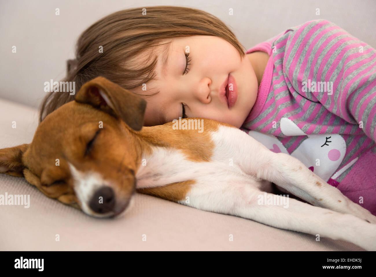 Toddler namorada dormindo ao lado de raça mista de cachorrinho Imagens de Stock