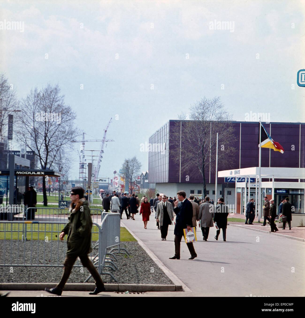 Besucher sehen sich die einzelnen Stände und Pavillons auf der Hannover Messe 1964 um. Visitantes e clientes Imagens de Stock