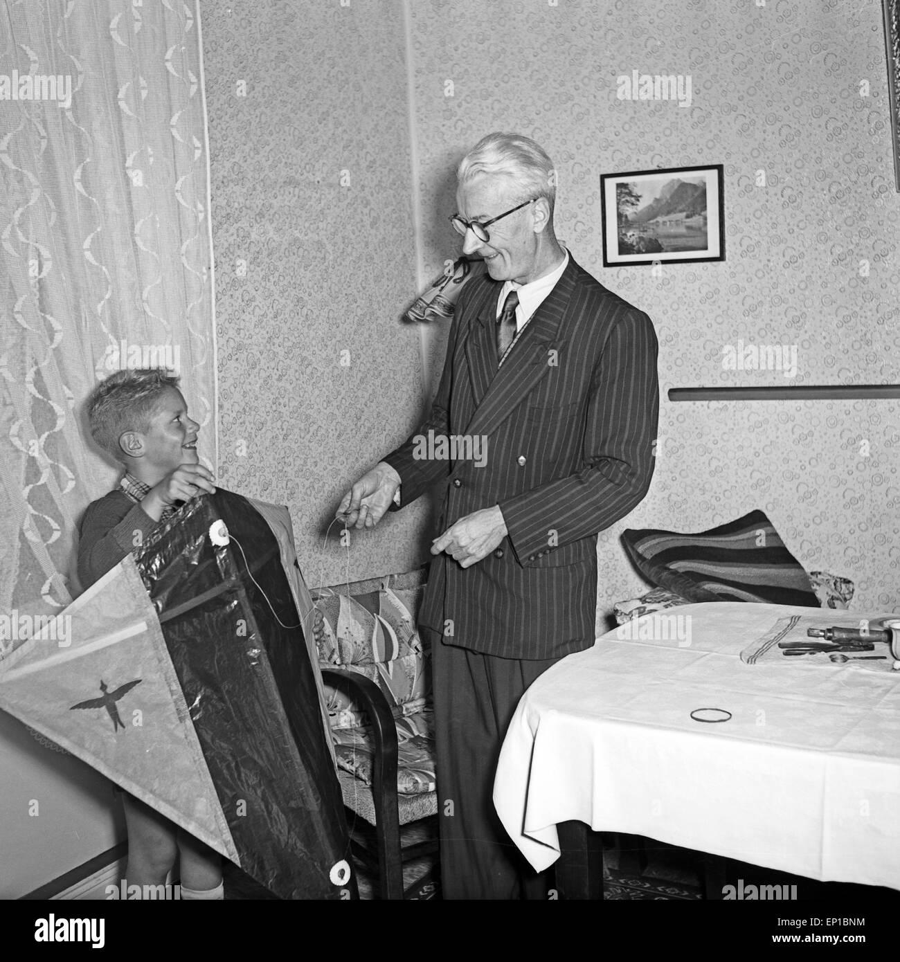 Ein älterer Herr gibt em seinem Wohnzimmer einem kleinen Jungen einen Lenkdrachen, Deutschland 1950er Jahre. Imagens de Stock