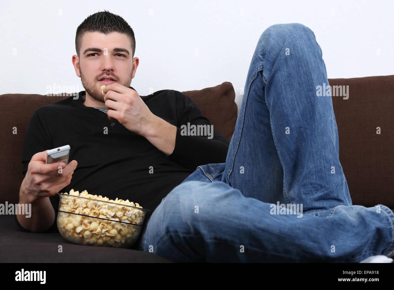 Junger Mann schaut fernsehen und isst Pipoca Imagens de Stock