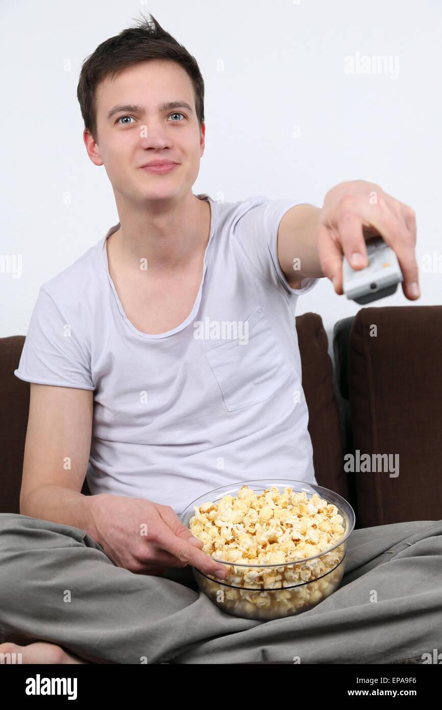 Junger Mann sitzt auf dem Sofá und schaut fernsehen Imagens de Stock