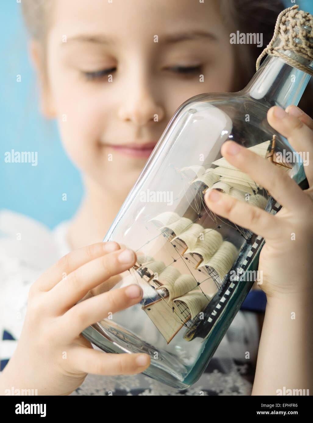 Menina segurando um brinquedo navio em garrafa Imagens de Stock