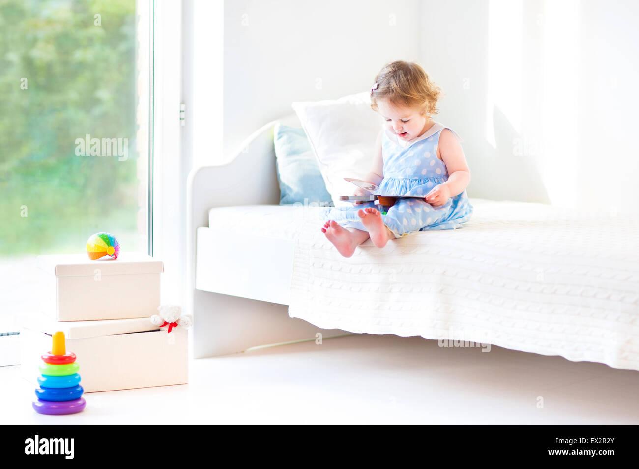 Adorável toddler Menina lendo um livro sentado em uma cama branca em uma grande janela com vista para o jardim Imagens de Stock