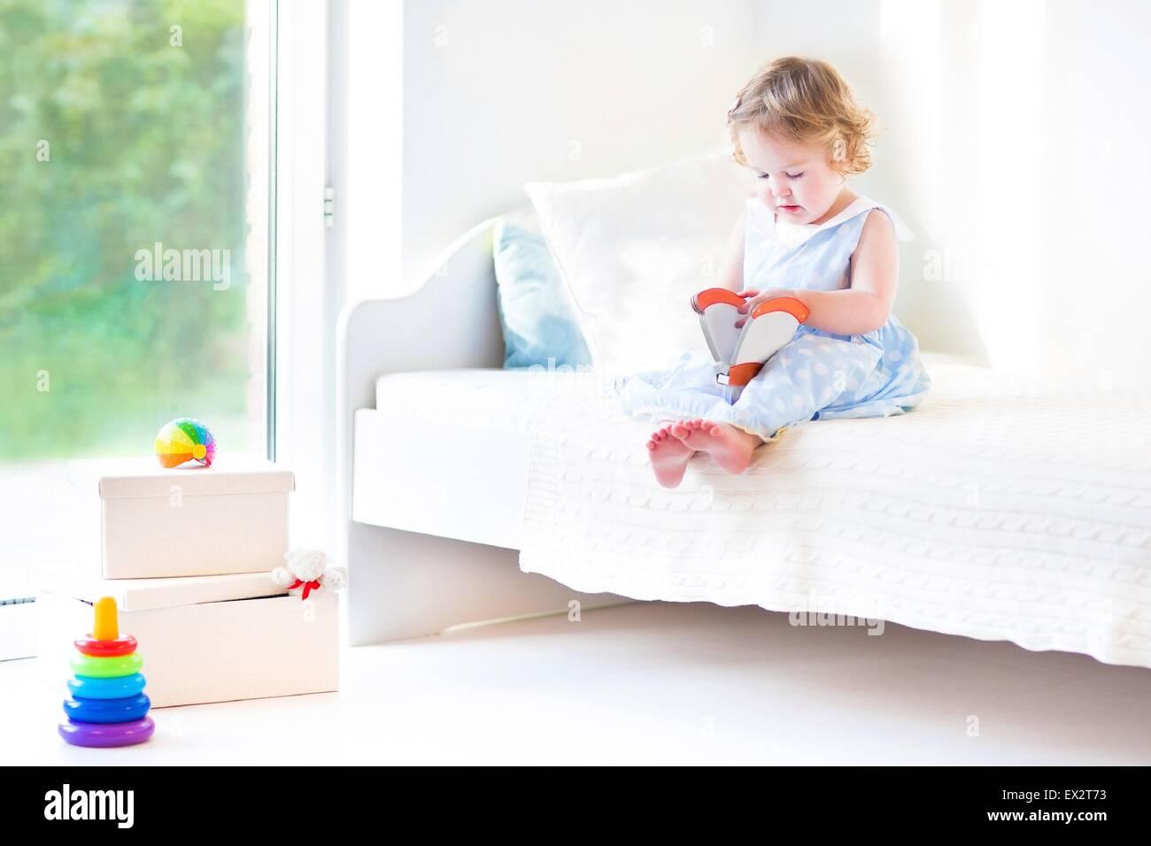 Belo cabelo encaracolado toddler Menina lendo um livro sentado em uma cama branca ao lado de uma grande janela com Imagens de Stock