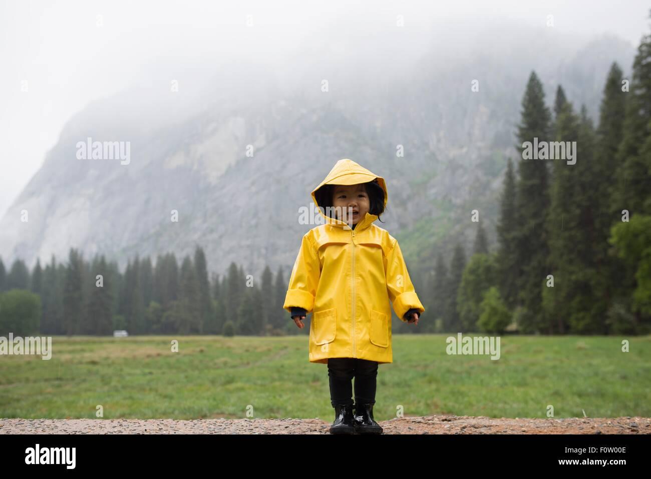 Retrato de crianças do sexo feminino vestindo gabardina amarela na frente da montanha enevoada, Parque Nacional Imagens de Stock