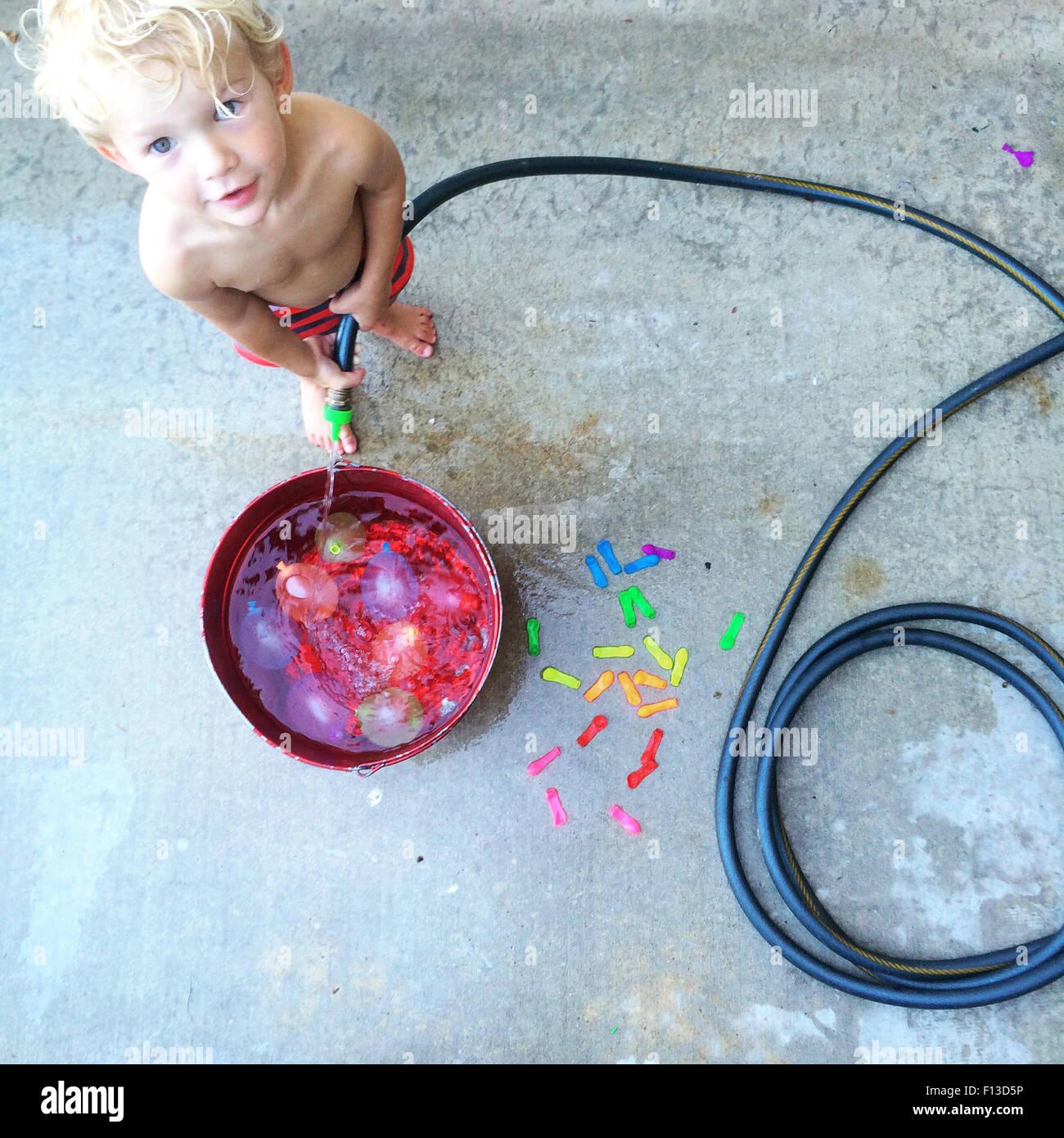 Toddler enchimento um balde com água Imagens de Stock
