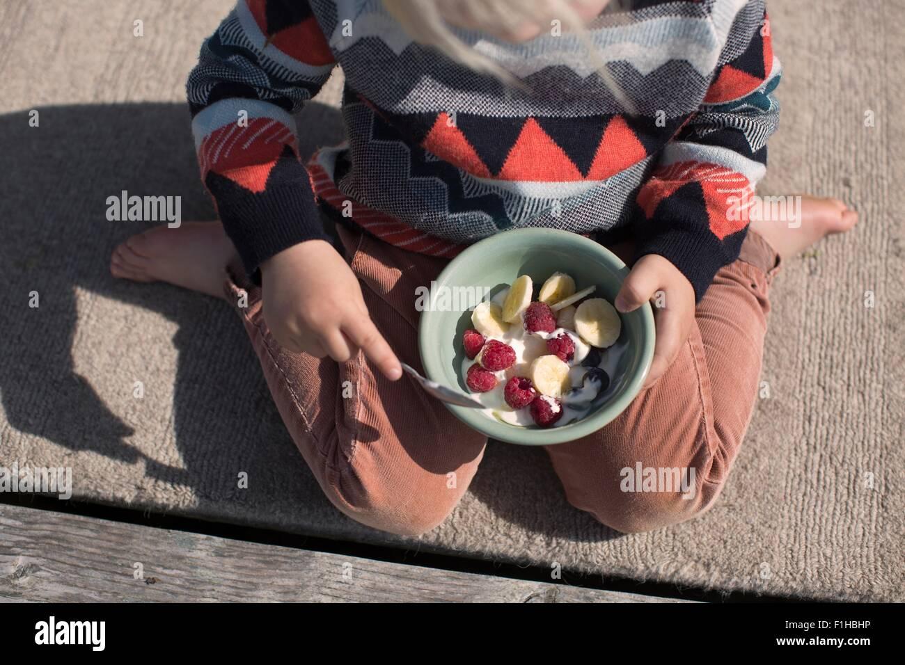 Boy exploração taça de fruta, ângulo alto Imagens de Stock