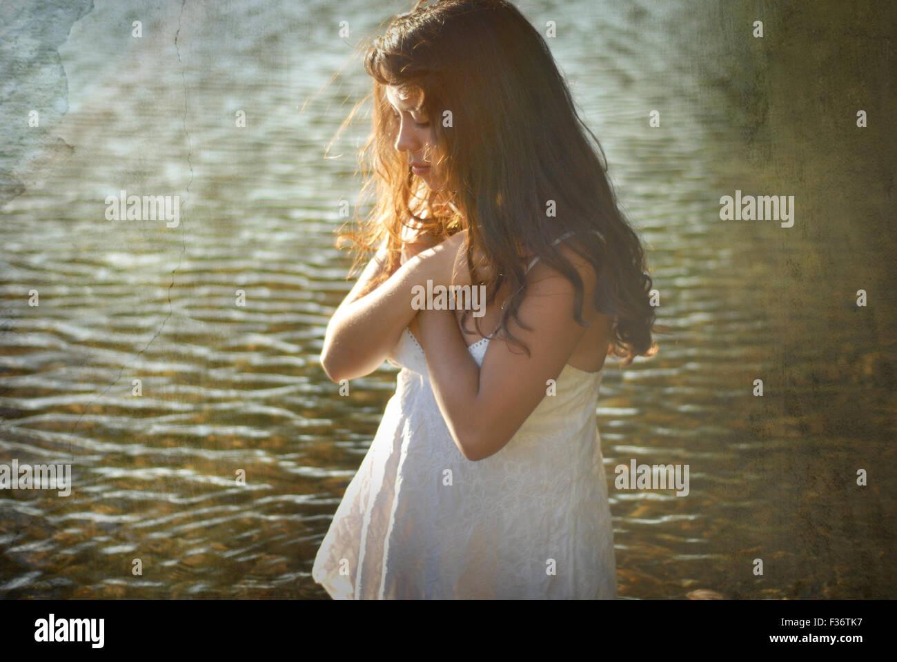 Menina cruz armas no rio de água verão vestido branco cabelos longos Imagens de Stock