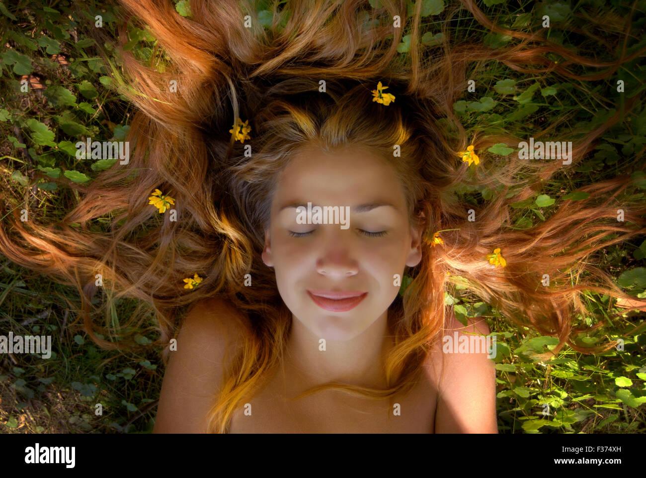 Linda rapariga loira cabelos longos na grama com flores na sua cabeça Imagens de Stock