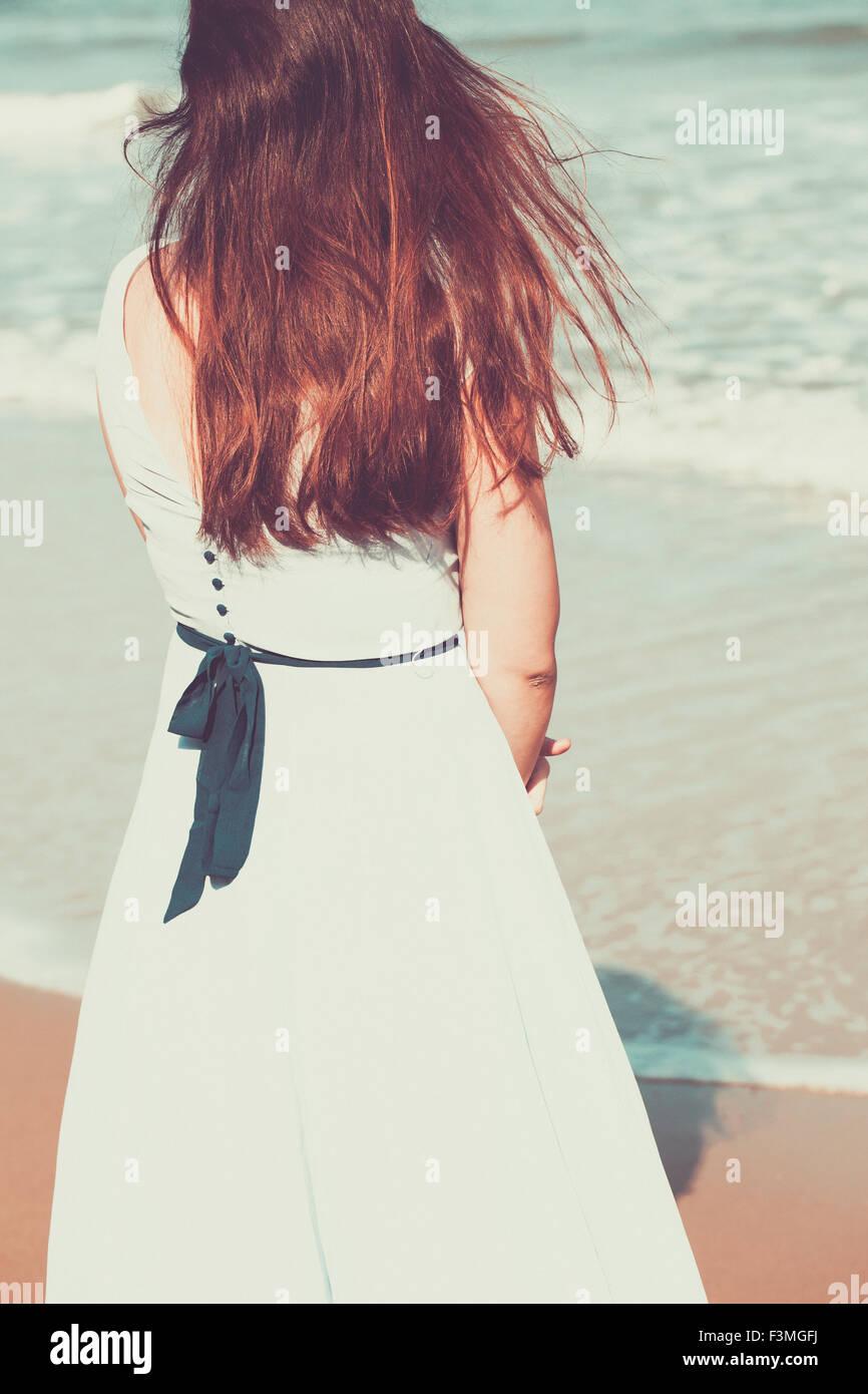 Histórico de jovem mulher na praia vestindo um vestido azul Imagens de Stock