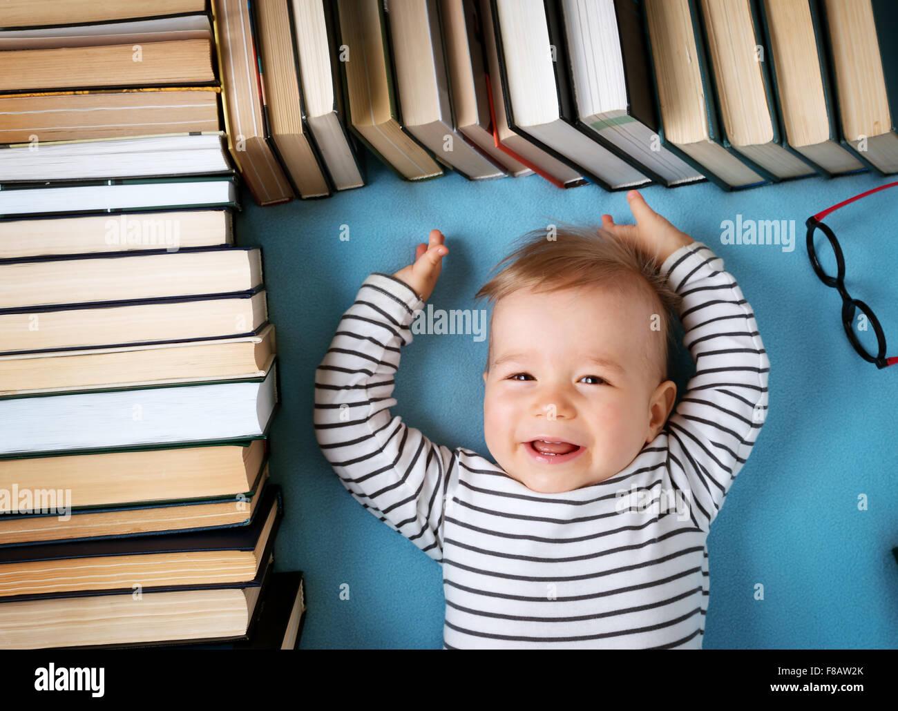 Um ano de idade bebé com spectackles e livros Imagens de Stock