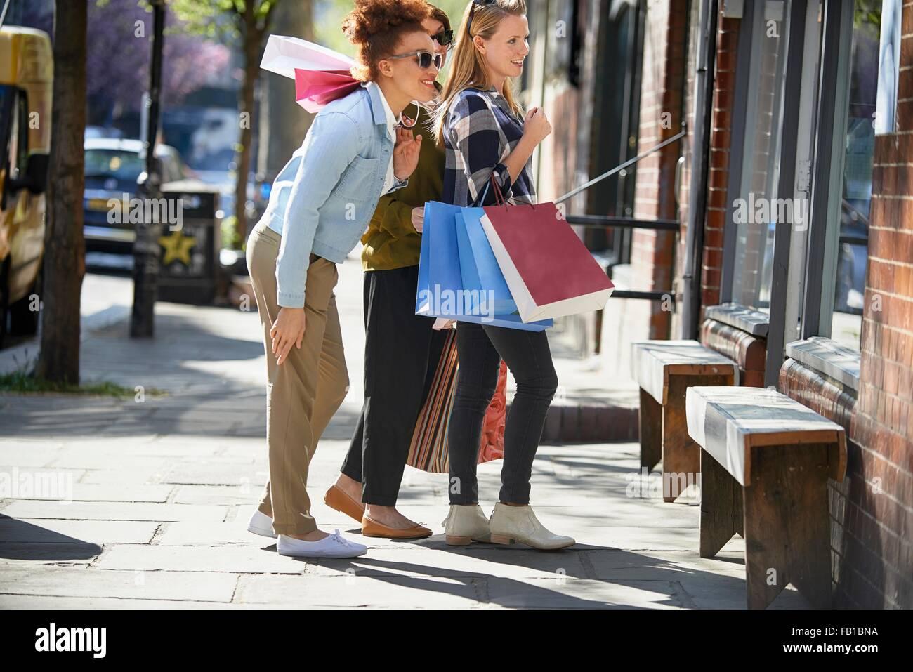 Vista lateral da exploração das mulheres sacos de compras na rua permanente olhando na janela de loja Imagens de Stock