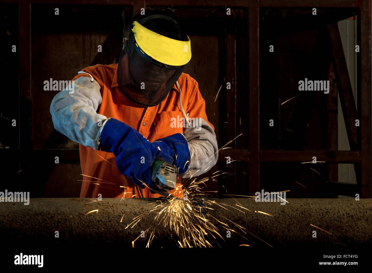 Trabalhador Industrial corte e solda de metal com muitos sharp faíscas Imagens de Stock