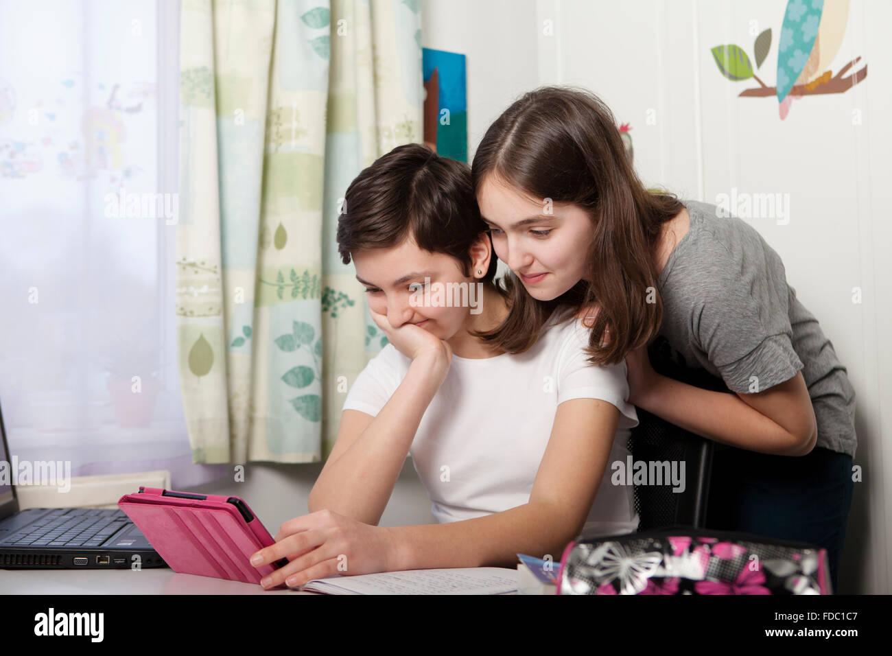 Duas Irmãs adolescentes em casa com tablet Imagens de Stock