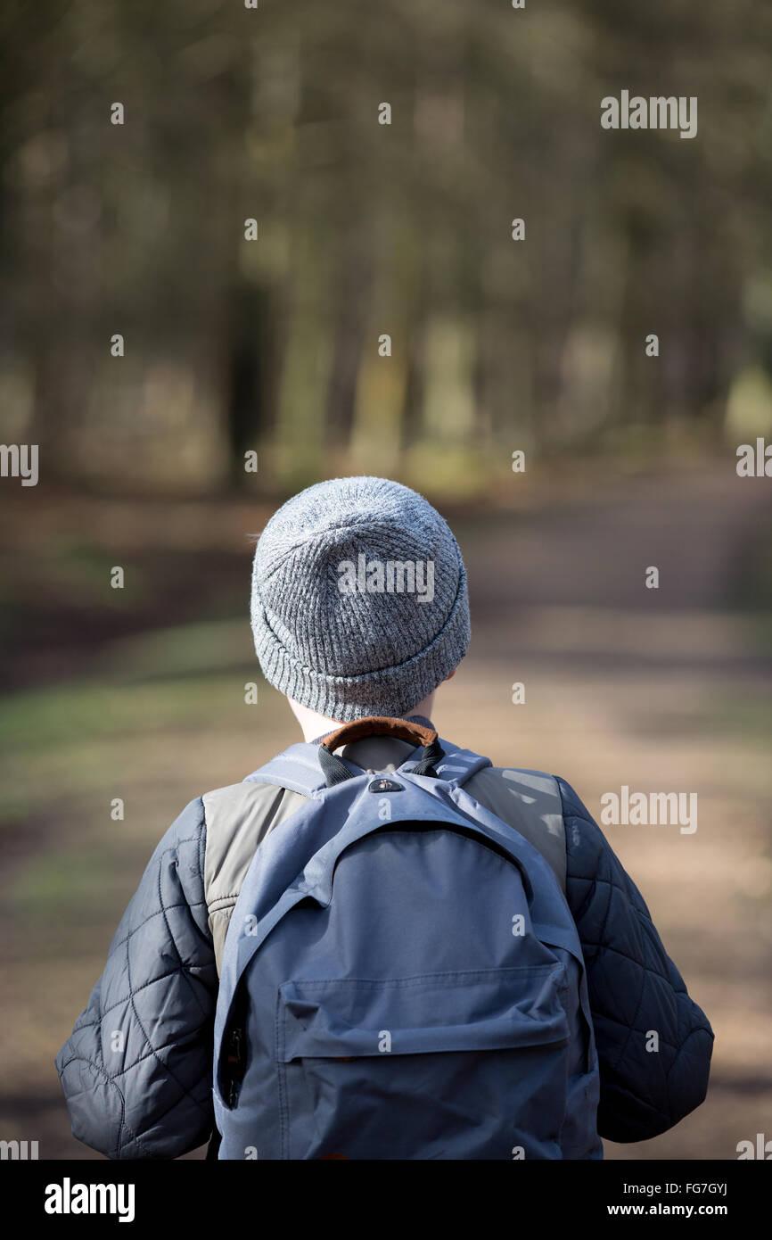 Um menino com uma mochila caminhada nos bosques Imagens de Stock