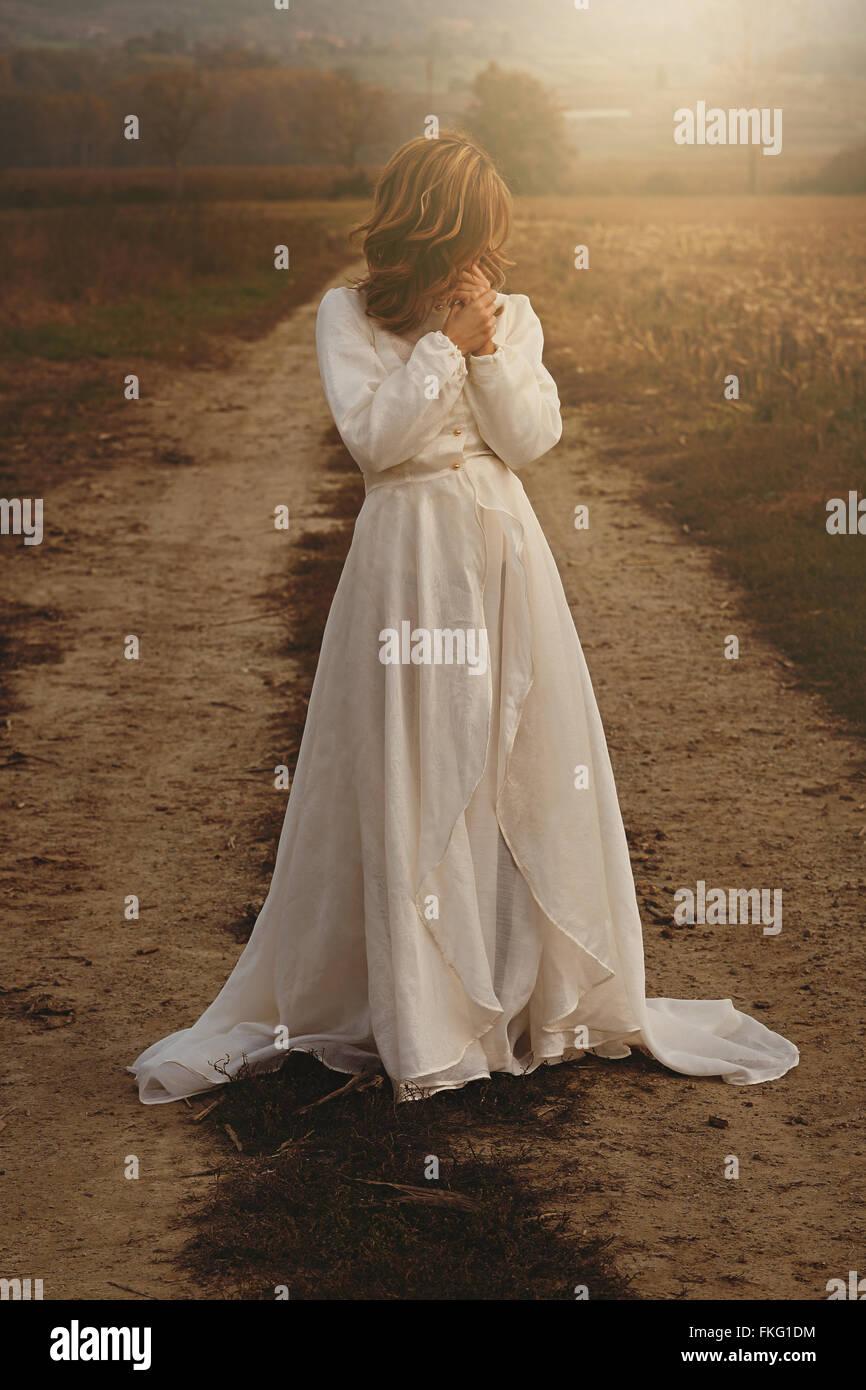 Mulher sozinha com vestido de noiva vintage no campo . A pureza e a inocência Imagens de Stock