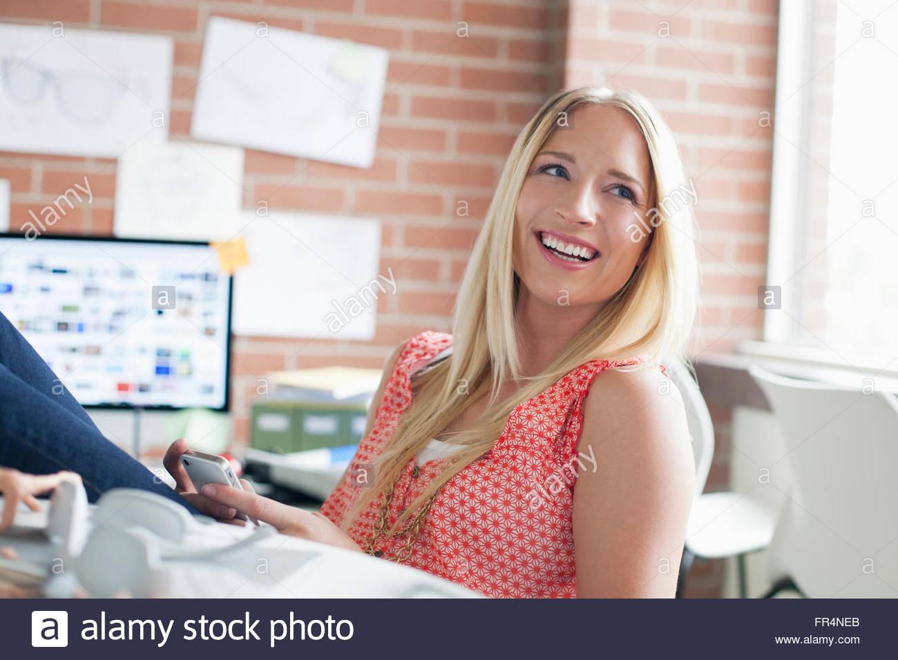 Bonito, designer industrial do sexo feminino com telefone smart Imagens de Stock