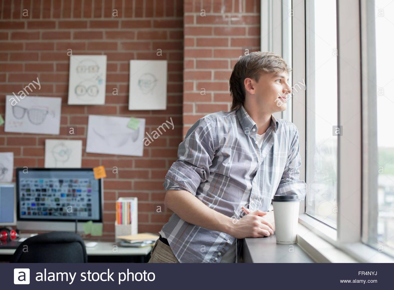 Os jovens do sexo masculino, designer industrial admiram a janela para fora Imagens de Stock