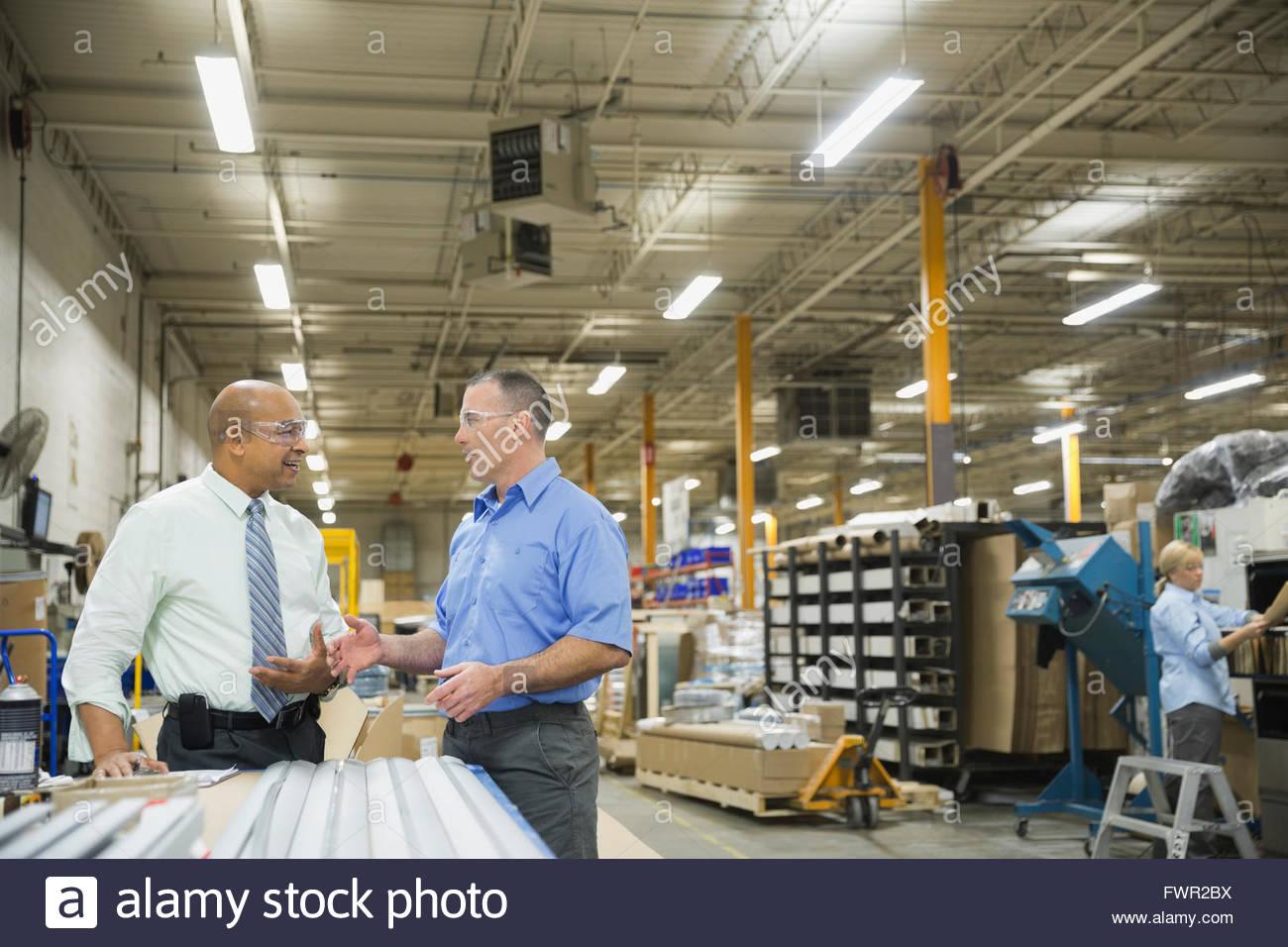 Manager e o trabalhador no depósito de fabricação de metal Imagens de Stock