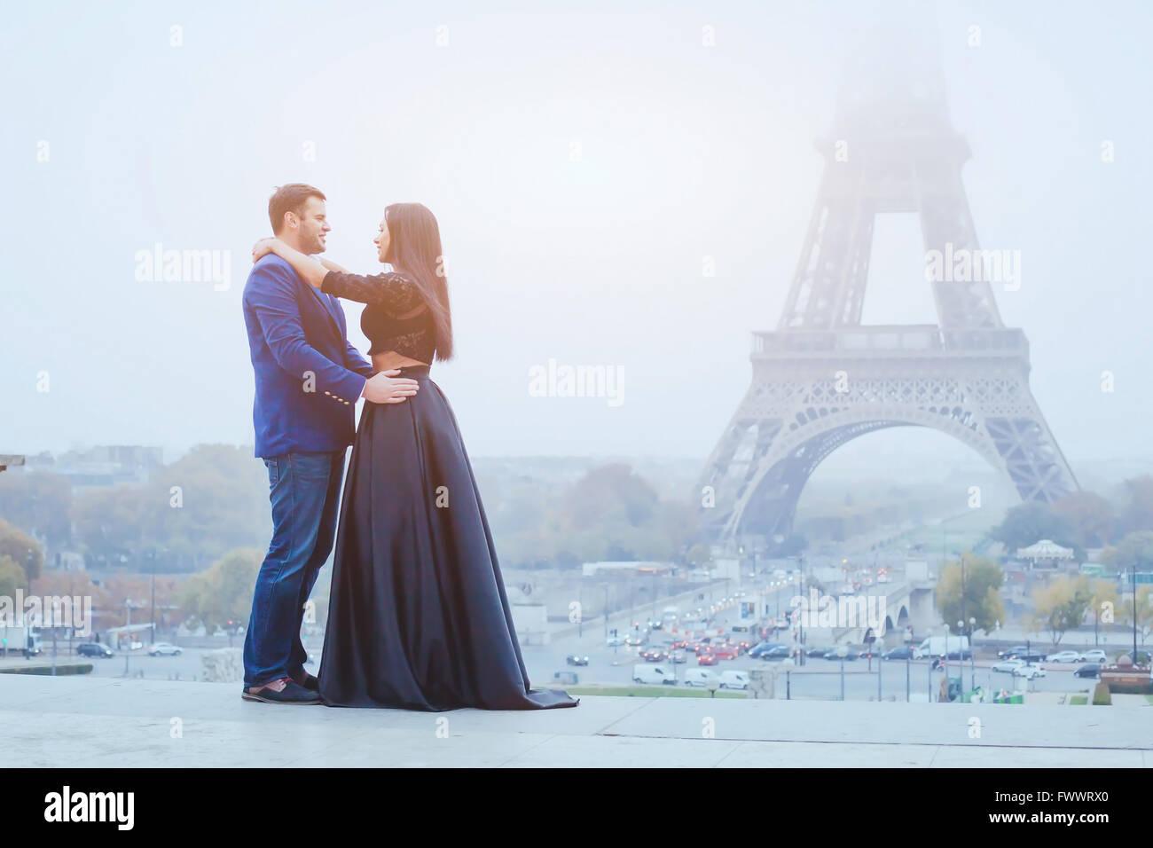 Casal feliz viajando em Paris, sorrindo o homem e a mulher colocam na fantasia moda roupas no fundo da torre Eiffel Imagens de Stock