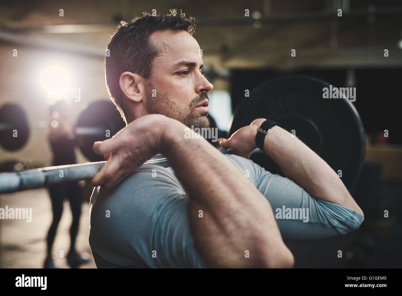 Aplicar jovem halteres elevação olhando focada, trabalhando em um ginásio com outras pessoas Imagens de Stock