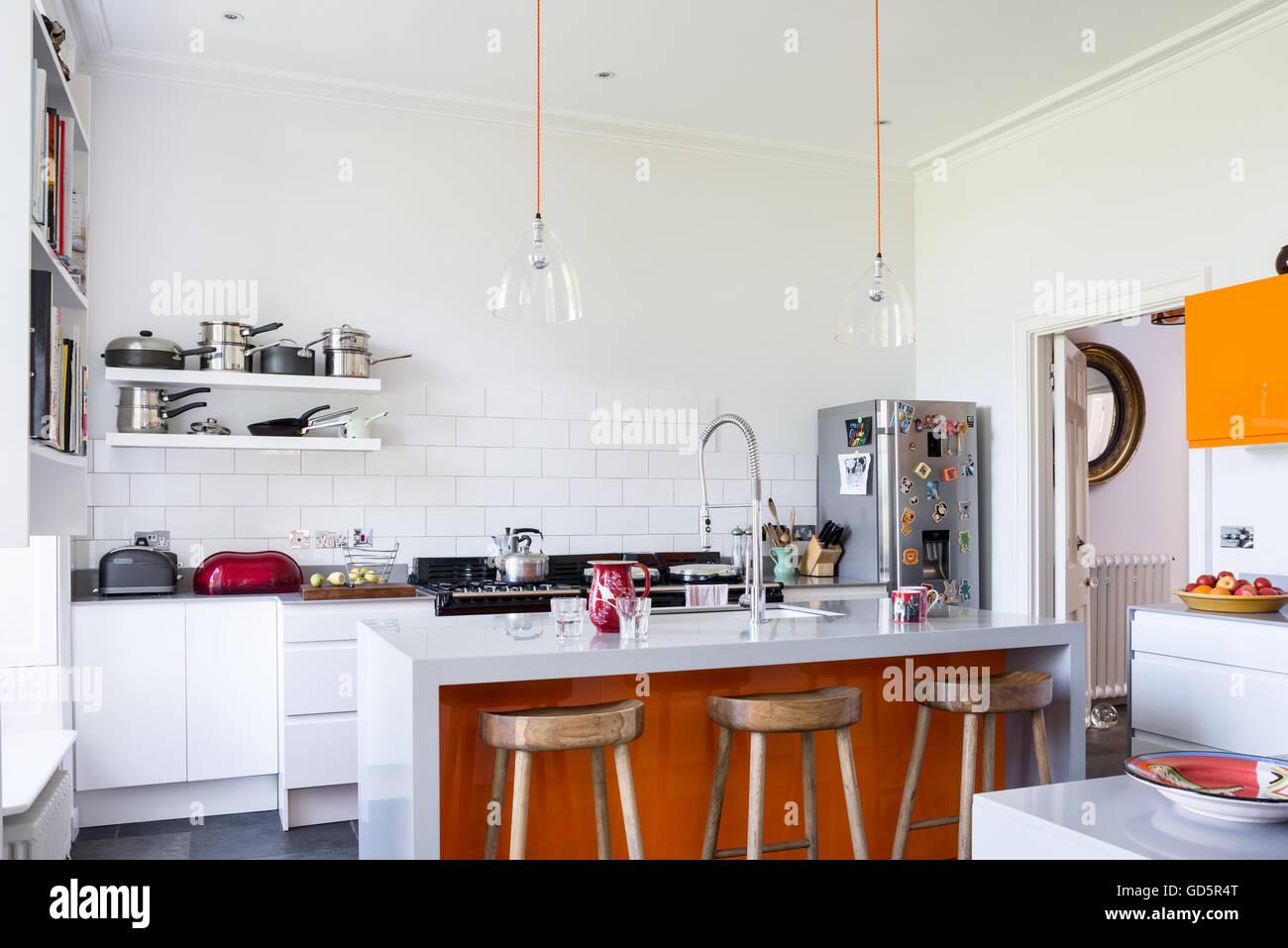 Bancos de bar de madeira em alta cozinha tectos altos com azulejos de metro branco. As luzes de teto de vidro transparente Imagens de Stock